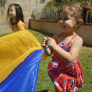 little preschool girl playing outdoors with giant colorful parachute