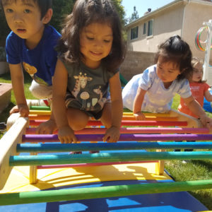 little preschool aged kids climbing on a colorful rainbow pikler triangle