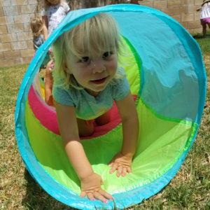 little preschool girl crawling through colorful tunnel outside