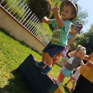 little preschool boy jumping off gymnastics foam wedge on grass