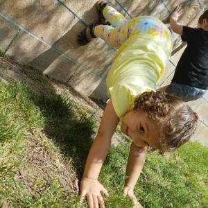 little preschool girl doing handstand against a brick wall